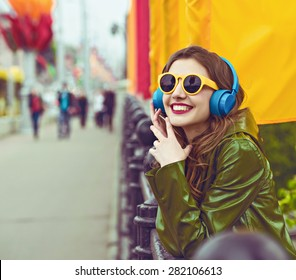outdoor street style hipster dj woman in yellow sunglasses and headphones listen music and smile