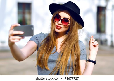 Outdoor street style image of young trendy woman making selfie on the street , wearing stylish hipster autumn hat, sensing kiss and playing with her hairs.