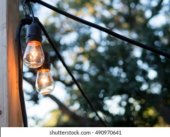 Outdoor string lights hanging on wood pole