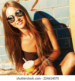 Outdoor summer closeup portrait of pretty smiling blonde woman in round sunglasses with cocktail