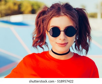 Outdoor summer colorful portrait of pretty young beautiful woman in sunglasses, having fun on the skatepark. Oudoor.