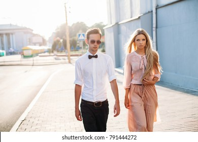 Outdoor summer evening portrait of stylish young couple walking on the street