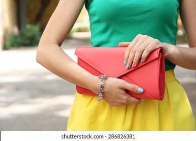 Outdoor summer fashion girl with orange clutch .