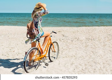 Outdoor summer  image of pretty happy woman riding bicycle on amazing beach . Wearing   bright  shirt, straw hat, boho  backpack.