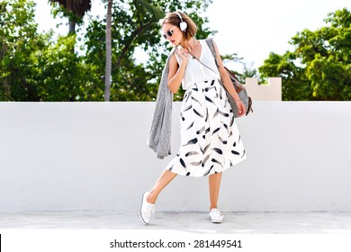 Outdoor summer lifestyle fashion portrait of young hipster stylish woman walking on the street, wearing vintage clothes and earphones, clear fresh colors.