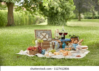Outdoor summer lifestyle with a gourmet picnic laid out on the grass in a park with bread rolls, berries, cheese, meat kebabs, pickles, red wine in stylish glasses and a vintage lantern on a hamper
