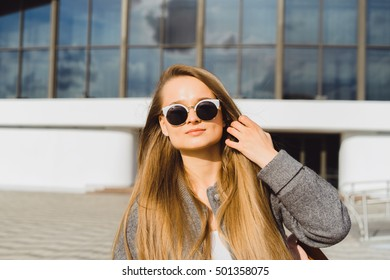 Outdoor summer lifestyle image of young pretty hipster woman having fun on the street,city center Europe,cute white vintage outfit and sunglasses,fun ,emotions.sunset.Outdoor fashion closeup portrait