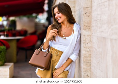 Outdoor summer lifestyle portrait of happy smiling young attractive brunette woman smiling and having fun , wearing modern casual summer elegant outfit and leather caramel bag, warm colors.