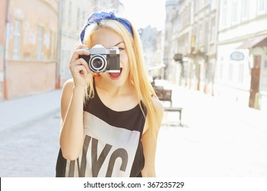 Outdoor summer lifestyle portrait of pretty woman having fun in city with camera. Travel photo of photographer. Making pictures, hipster style. Blonde girl looking at camera. Young woman taking photo