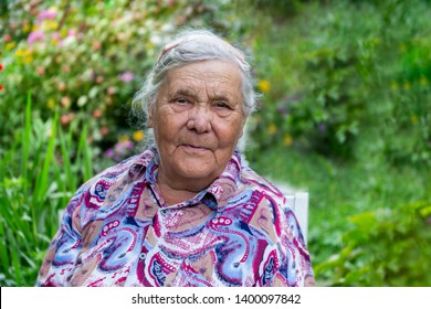 Outdoor summer portrait of an eldery seniour woman, close-up, grandmother of 80-90 years old in the garden looking at the camera.