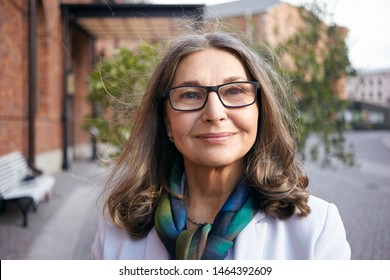 Outdoor summer portrait of good looking Caucasian businesswoman in her sixties wearing rectangular spectacles, jacket and silk scarf around her neck smiling, going to office after lunch break