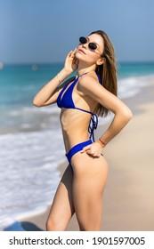 Outdoor summer portrait of pretty young smiling happy woman in sunglasses and bikini posing near the sea