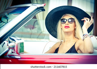 Outdoor summer portrait of stylish blonde vintage woman driving a convertible red retro car. Fashionable attractive fair hair female with black hat in red vehicle. Sunny bright colors, outdoors shot.