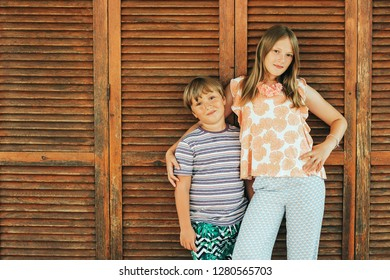 Outdoor summer portrait of two funny kids, small brother and big sister