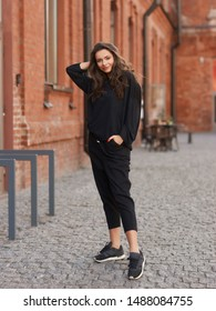 Outdoor summer portrait. Young elegant woman in black hoodie and trousers standing and posing at urban city street