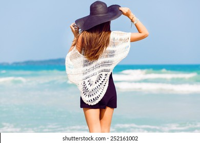 Outdoor summer portrait of young pretty woman looking to the ocean at tropical beach, enjoy her freedom and fresh air, wearing stylish hat and clothes.
