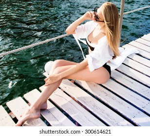 Outdoor summer portrait of young pretty woman looking to the ocean at tropical beach, enjoy her freedom and fresh air, wearing stylish clothes.