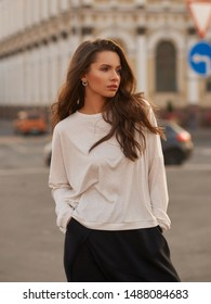Outdoor summer portrait. Young stylish woman in white hoodie and black trousers standing and posing at city street at sunset