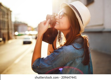 Outdoor summer smiling lifestyle portrait of pretty young woman having fun in the city in Europe in evening with camera travel photo of photographer Making pictures in hipster style glasses and hat