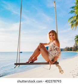 Outdoor summer vacation tropic palm style portrait of young smiling blonde sexy woman posing in bikini on beach swing blue water and sky