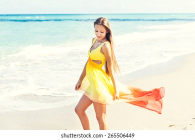 outdoor sunny picture of a beautiful sexy girl in her amazing dress walking down the beach at her summer vacation