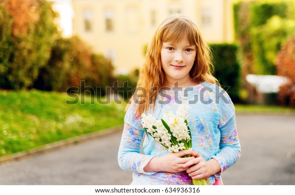 Outdoor sunny portrait of a kid girl with white Hyacinth flowers