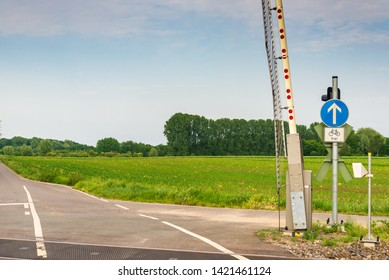 """Outdoor sunny street view of level crossing railway barrier, traffic light and symbol of bicycle"""" Frei """" free lanes sign at intersection between road and railway in Meerbusch, Germany."""