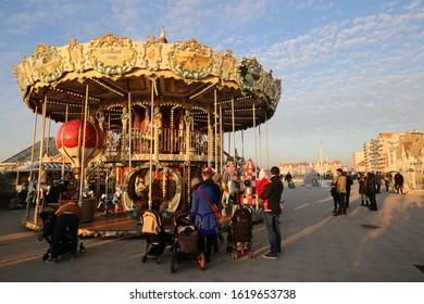Outdoor sunny view of a carousel wheel on the esplanade of le touquet paris plage city, nord pas de calais department, hauts de france region, France. December, 31, 2019. Pedestrians walking.