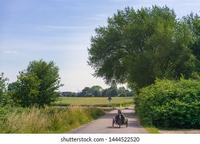 Outdoor sunny view of cyclist ride a Recumbent Bike on small road in suburb area surrounded with agricultural field with fresh growing green wheat field in summer season against blue sky in Germany.
