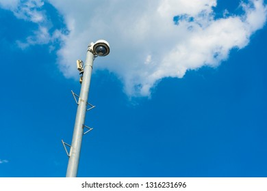 Outdoor surveillance video camera on a pole on clear blue sky.