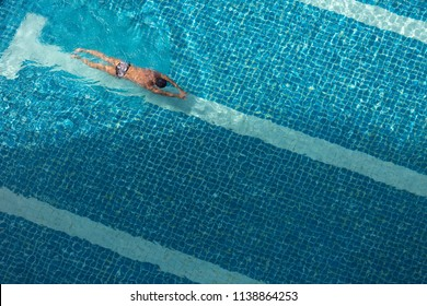 Outdoor swimming pool background. A male swimmer is floating on the water surface while swimming alone in the outdoor pool during summer season in Thailand.