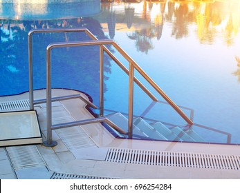 outdoor swimming pool in-pool ladder with trees and umbrellas reflection in water, sunlight toned effect