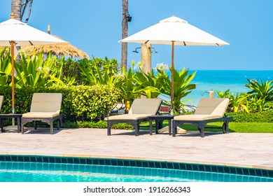 Outdoor swimming pool with sea ocean beach around umbrella and chair for leisure travel vacation