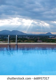 Outdoor swimming pool with sunbeam over mountains