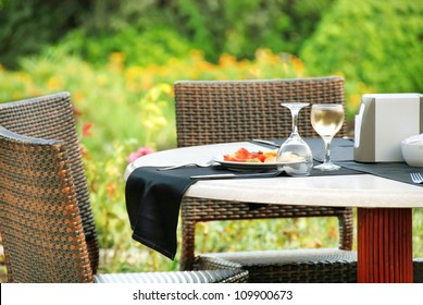 outdoor table with served plate and wine glasses