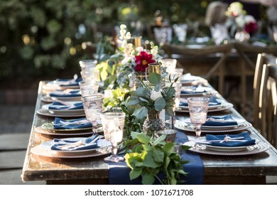 Outdoor table set up for wedding reception with flowers and antique fixtures.