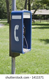 Outdoor telephone booth payphone in a public park.