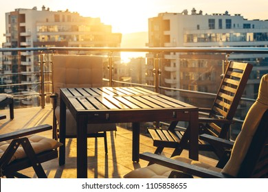 Outdoor Terrace With Garden Furniture In The Background Of The City And Sunset. Luxury Apartments Resort Recreation Summer Concept