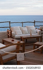 Outdoor terrace lounge facing infinity deep blue ocean and clear sky