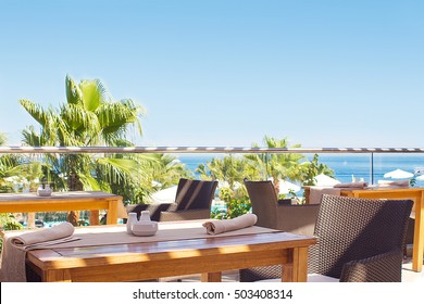 outdoor terrace of restaurant overlooking the sea and palm trees