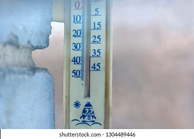 The outdoor thermometer on the wall of the house shows a very low temperature of 35 degrees Celsius below zero in frost in winter. Shot through the window glass.