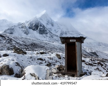 Outdoor toilet in Himalayas mountains. Unusual and funny outdoor toilet location in snowy mountains on Everest Base Camp Trek. Portal or escape from cold winter to hot summer.