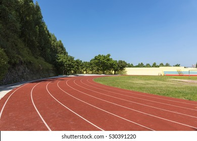 Outdoor track and field stadium runway under the blue sky.