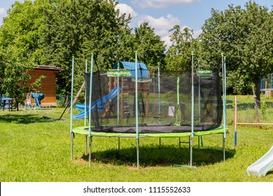 Outdoor Trampoline with safety net with Zipper entrance. Garden big Trampoline on green grass on Playground in the yard. Open Jump Trampolining.