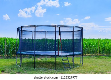 Outdoor Trampoline with safety net with Zipper entrance.  Garden big Trampoline on the green grass near the corn field on blue sky background. Open Jump Trampolining
