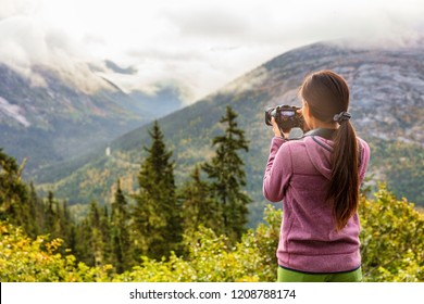 Outdoor travel lifestyle woman photographer shooting video camera at Alaska background. USA vacation holiday in Autumn.