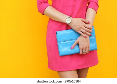 Outdoor trendy girl near yellow street wall .Pink dress and blue clutch.