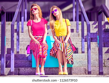 Outdoor. Two Model Girl on Urban stone steps. Young Playful Woman posing with Sister in Stylish Sunglasses, Trendy Fashion Summer Outfit. Attractive Blond Redhead. Creative.