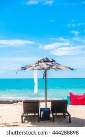 Outdoor with umbrella and chair on beautiful tropical beach and sea and blue sky background
