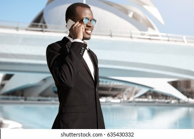 Outdoor urban shot of handsome young African American man wearing black formal suit and sunglasses having phone conversation after got desired position in large company, standing in urban setting